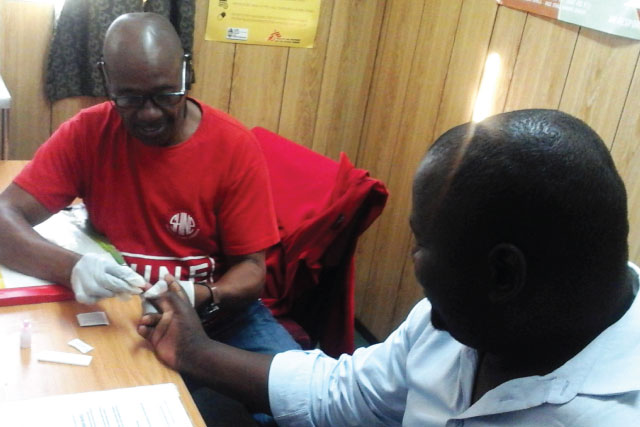 SHINE male-services counselor Zithulele Khanyile conducts an HIV test for a male patient